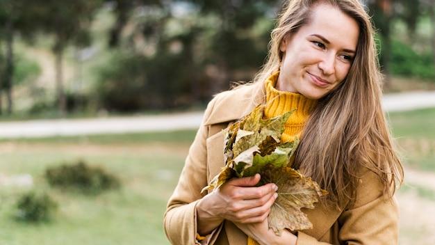 Женщина, держащая кучу листьев Бесплатные Фотографии