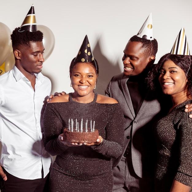 Женщина держит торт в окружении друзей Бесплатные Фотографии