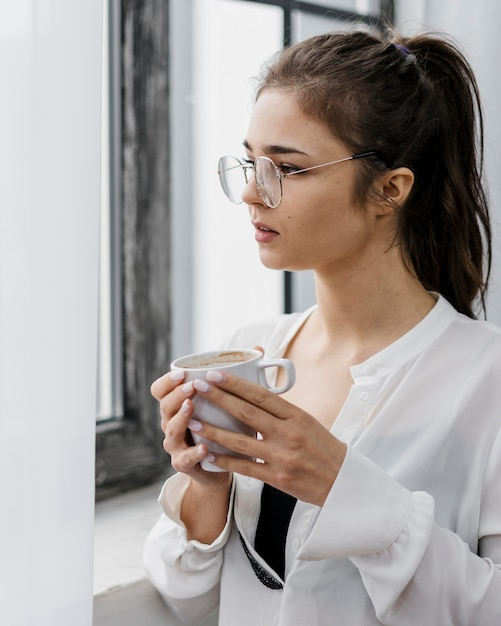Женщина, держащая чашку кофе во время работы из дома Бесплатные Фотографии