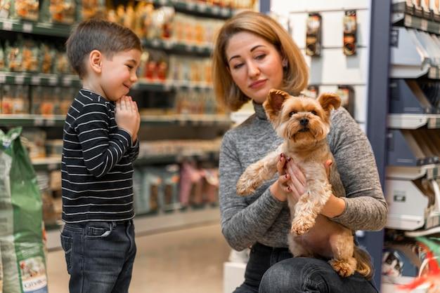 ペットショップでかわいい小さな犬を抱いている女性 無料写真