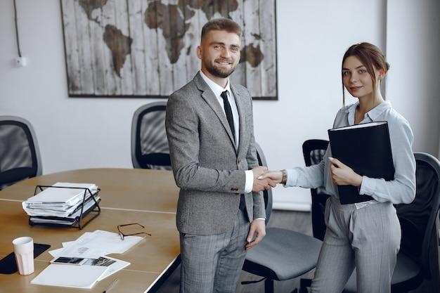 Женщина держит папку в руках. бизнесмен в своем офисе. коллеги пожимают друг другу руки Бесплатные Фотографии