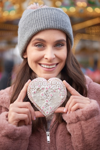 Женщина держит имбирное печенье в форме сердца Бесплатные Фотографии