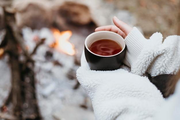 Женщина держит чашку горячего чая на открытом воздухе Бесплатные Фотографии