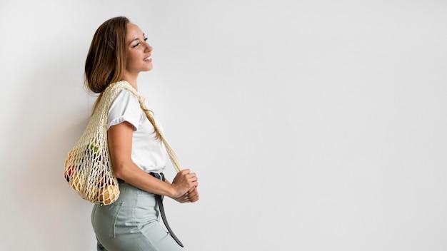 Женщина, держащая перерабатываемый мешок с копией пространства Бесплатные Фотографии