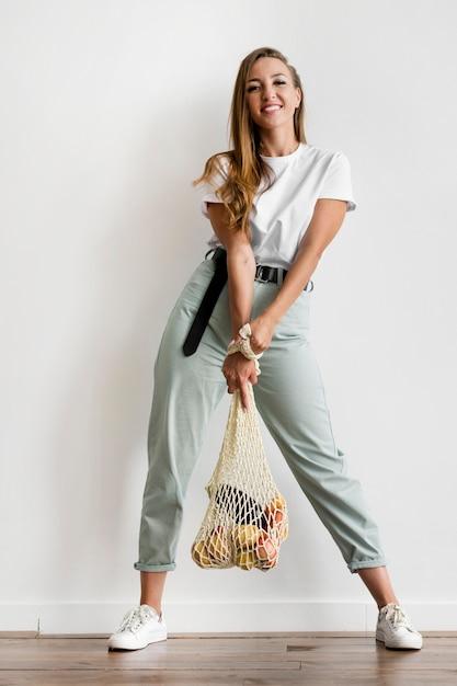 Женщина, держащая перерабатываемый мешок со здоровой пищей Бесплатные Фотографии