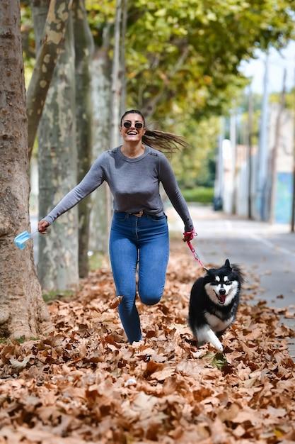 サージカルマスクを持った女性と通りの乾燥した葉の上を走っている美しい犬。 無料写真