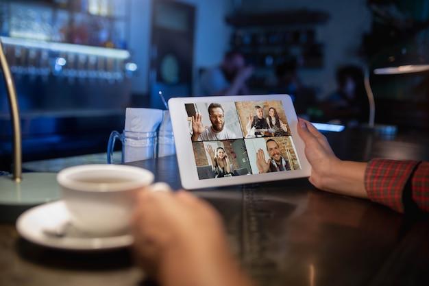 Женщина, держащая планшет для видеозвонка, попивая кофе Бесплатные Фотографии