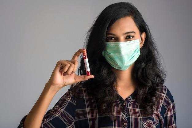 Женщина, держащая пробирку с анализом крови на коронавирус или анализ 2019-нков. Premium Фотографии