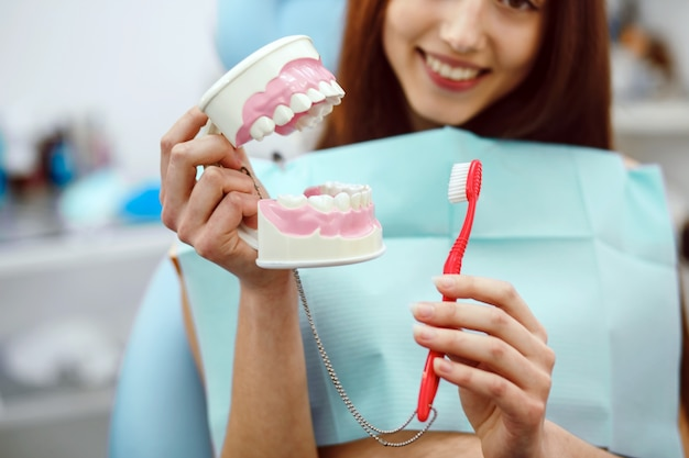 Woman holding a toothbrush and a dental mold Free Photo