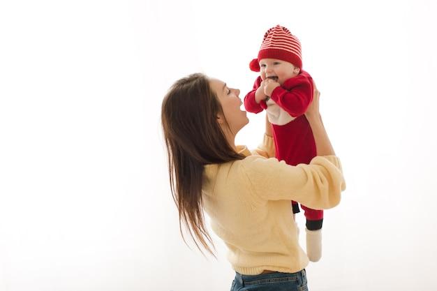 Женщина, держащая очаровательного малыша в праздничном костюме Premium Фотографии