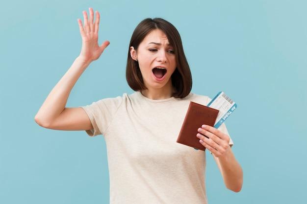 Женщина, держащая билеты на самолет и паспорт Бесплатные Фотографии