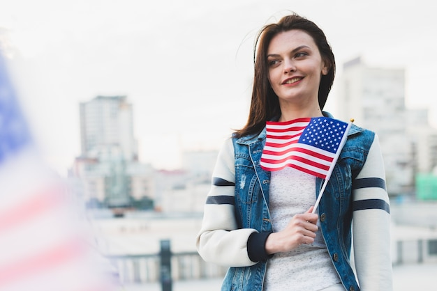 Woman holding american flag near chest Free Photo