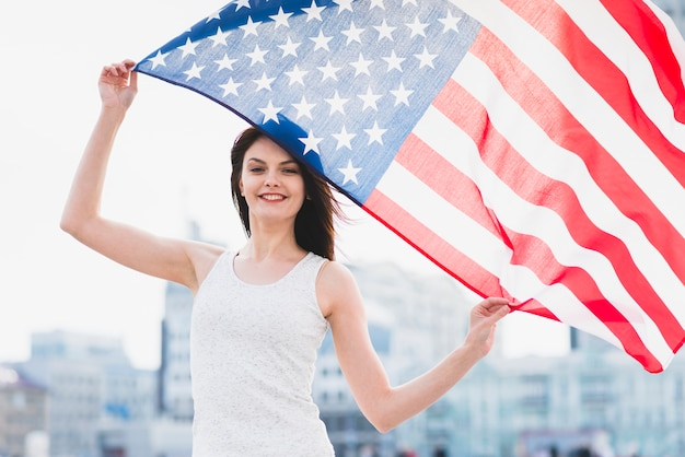 Woman holding american flan and waving it Free Photo