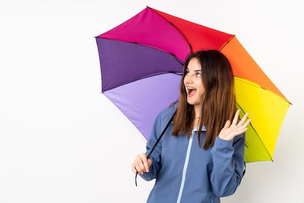 Женщина держит зонтик на белом с удивленным выражением лица Premium Фотографии