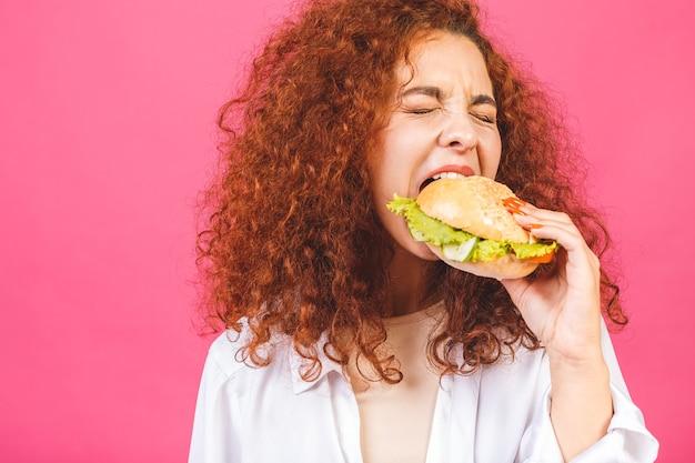 大きなハンバーガーを持って食べる女性 Premium写真