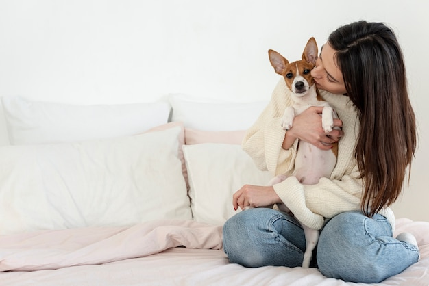 Женщина держит и целует ее собаку Premium Фотографии