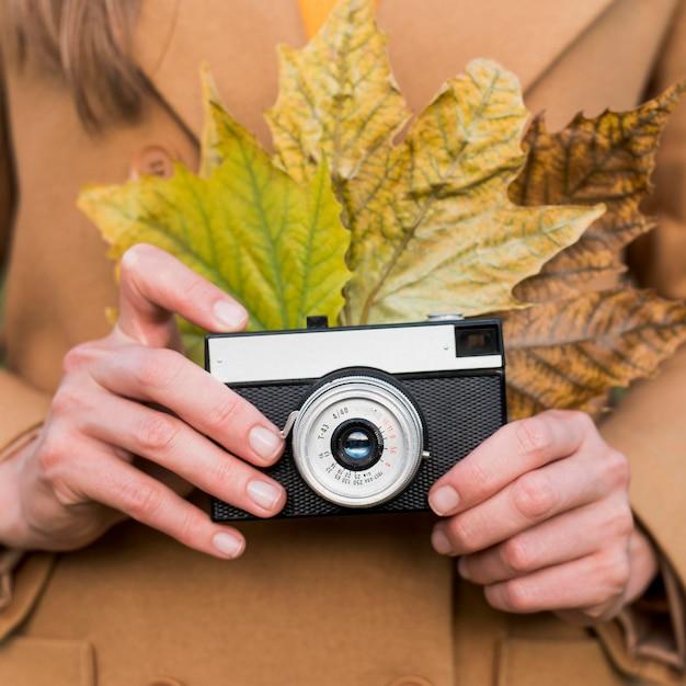 Женщина, держащая осенние листья и ее камеру Бесплатные Фотографии