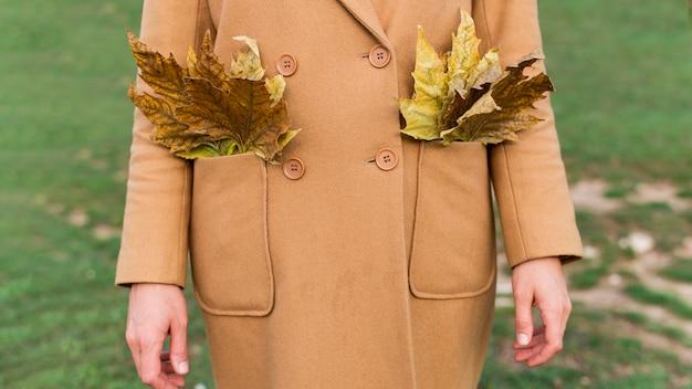 Женщина, держащая осенние листья в ее карманах Бесплатные Фотографии