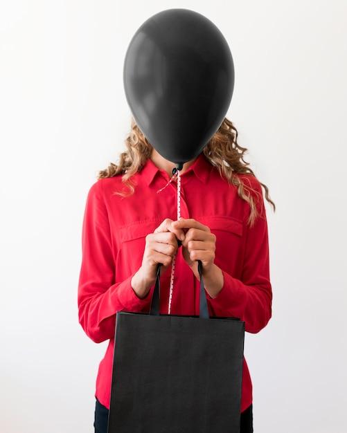 バッグと彼女の顔を覆っている黒い風船を保持している女性 無料写真
