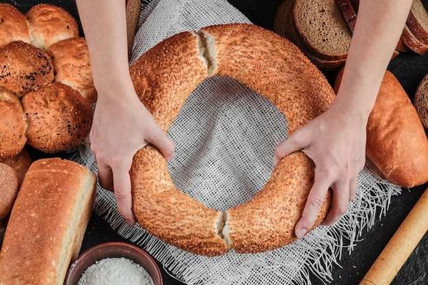 Woman holding bagel on dark table with various bread. Free Photo