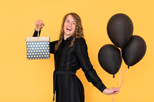 Woman holding balloons and gift box Free Photo
