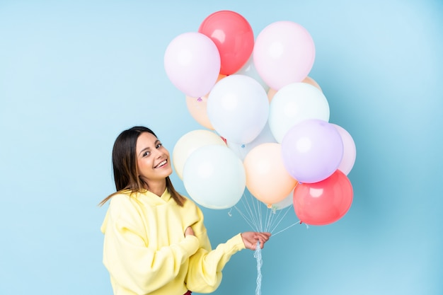 Woman holding balloons in a party over isolated blue wall laughing Premium Photo