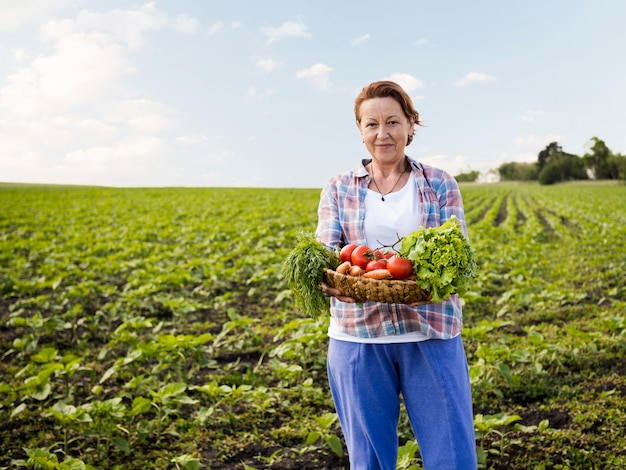 Woman holding a basket full of vegetables with copy space Free Photo