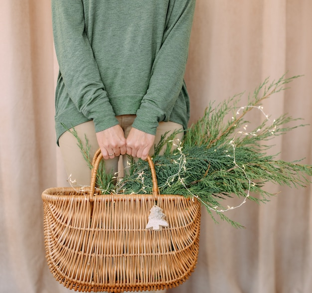 Woman holding a basket with christmas needles and a symbol wooden toy deer Premium Photo