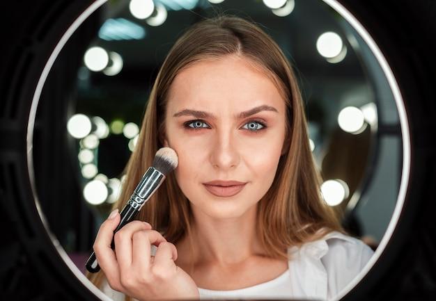 Woman holding big brush looking at mirror Free Photo