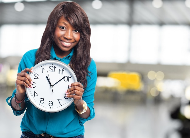 Woman holding a big clock Free Photo