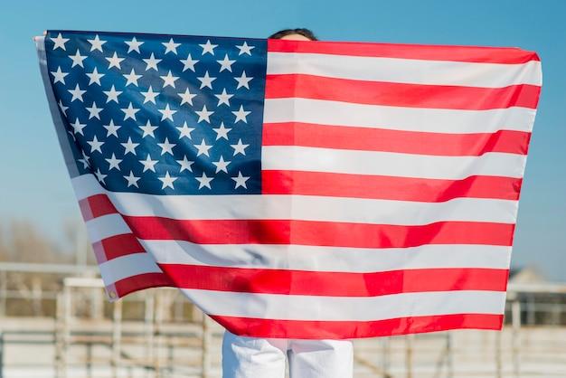 Женщина держит большой флаг сша над собой Бесплатные Фотографии