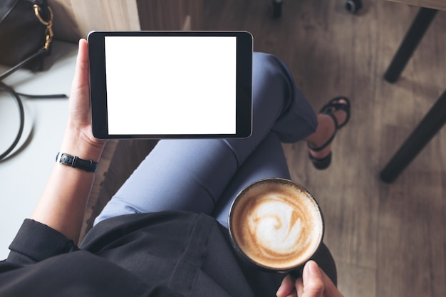 Woman holding black tablet pc with blank desktop screen while drinking coffee Premium Photo