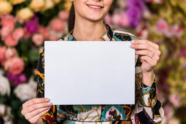 Woman holding blank paper in green house Free Photo
