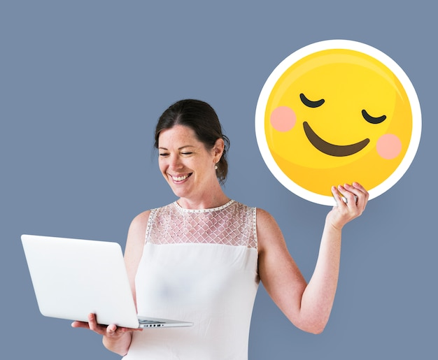 Woman holding a blushing emoticon and using a laptop Free Photo