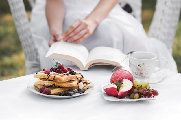 A woman holding book in hand with breakfast on white table at domestic garden Free Photo