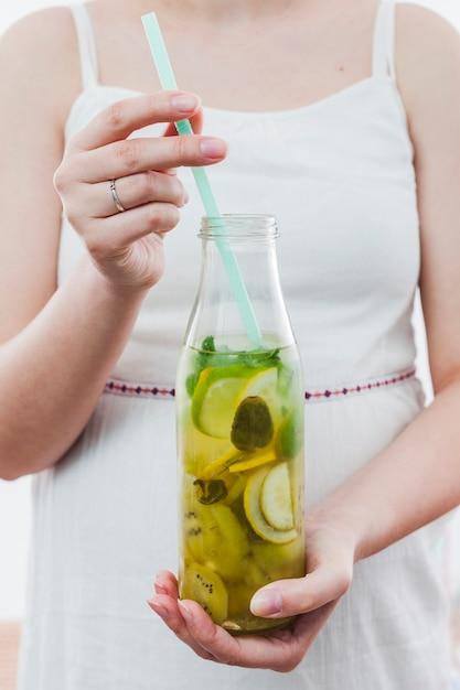Woman holding bottle of green lemonade Free Photo