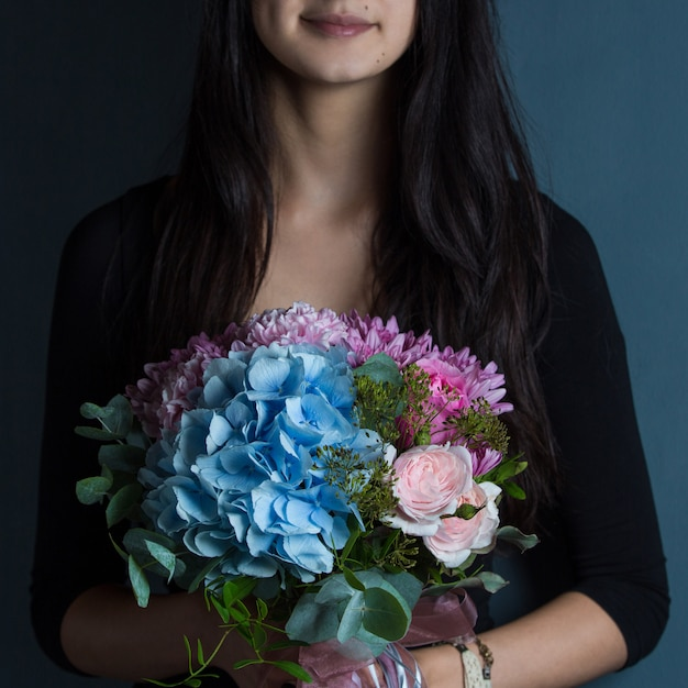 A woman holding a bouquet of flowers in the hand Free Photo