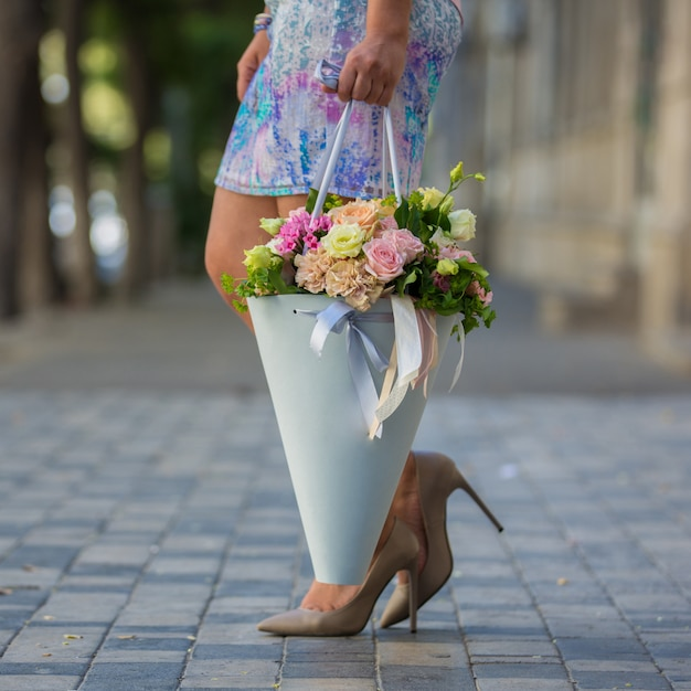 Woman holding a bouquet of flowers in the street view Free Photo