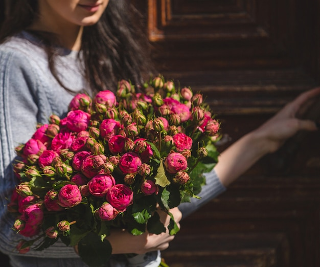 A woman holding a bouquet of pink peonies in the hand Free Photo