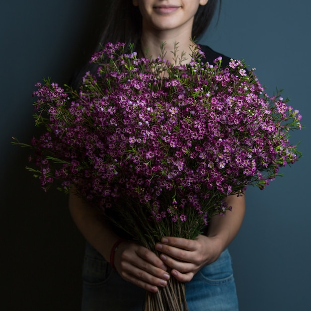 A woman holding a bouquet of purple sirens in the hand on a room wall backgorund. Free Photo