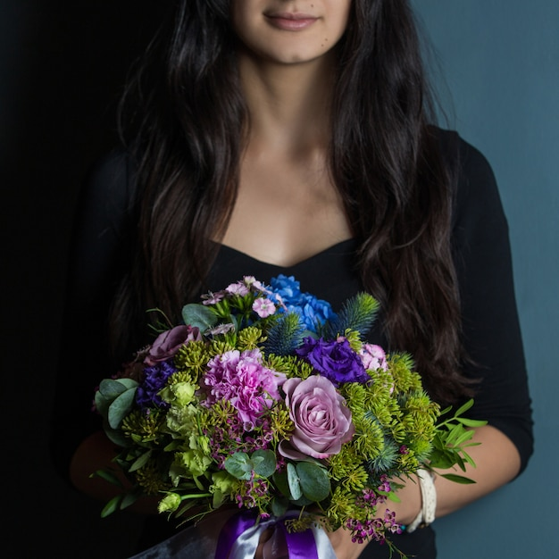 A woman holding a bouquet of seasonal flowers in the hand Free Photo
