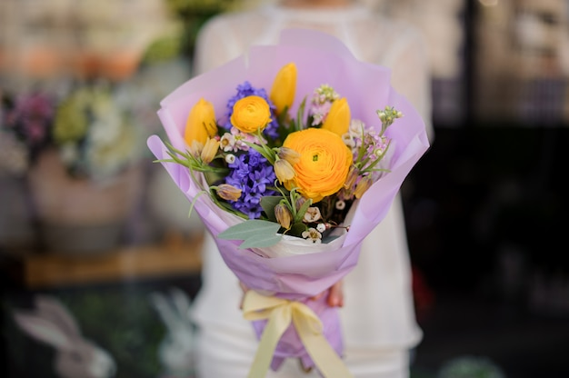 Woman holding a bouquet of yellow peony roses and violet blue hyacinth Premium Photo