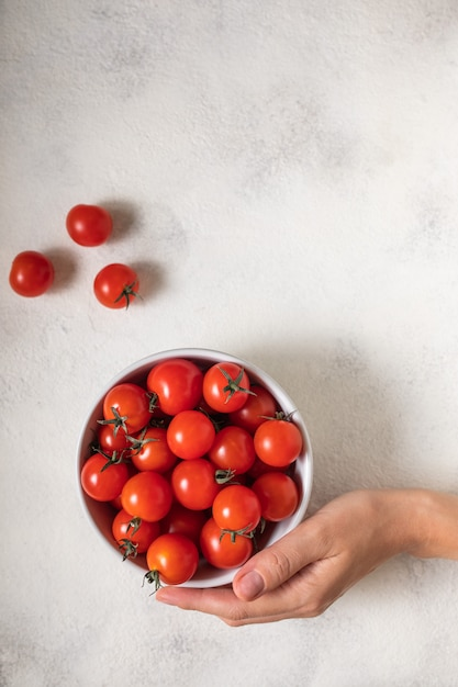 Woman holding bowl with ripe cherry tomatoes at table, above view Premium Photo