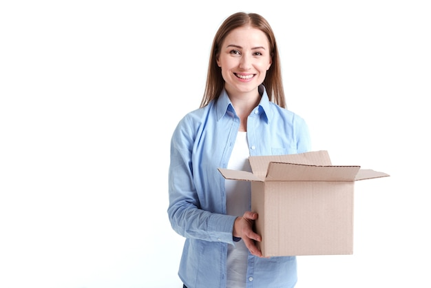 Woman holding a box and smiles Free Photo