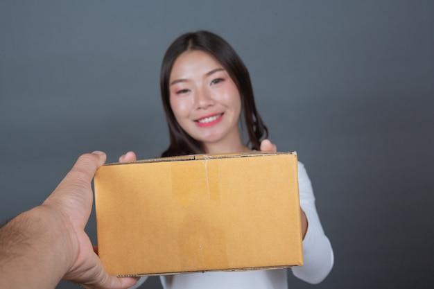 Woman holding a brown post box made gestures with sign language. Free Photo