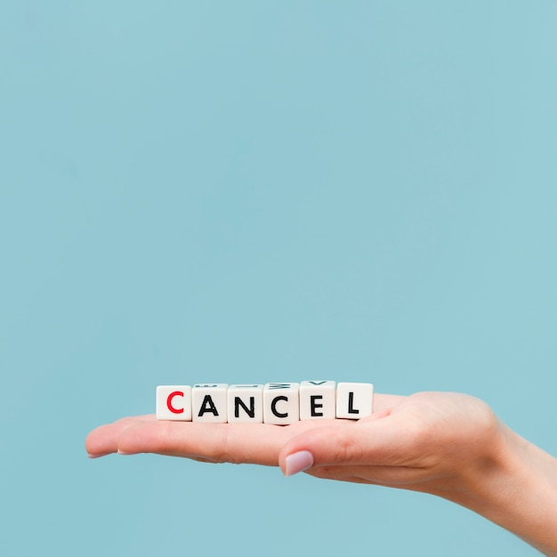 Woman holding a canceled message made from little cubes with copy space Premium Photo