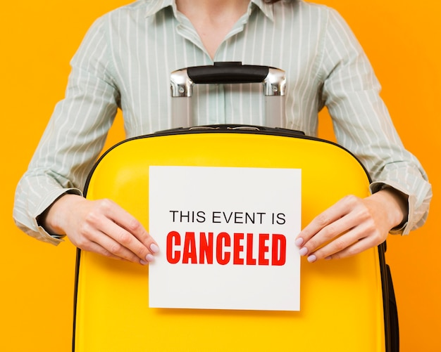 Woman holding a cancelled event card Free Photo