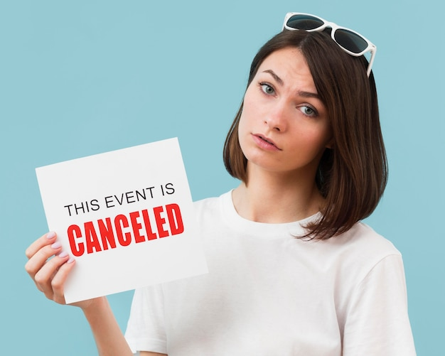 Woman holding a card with a canceled event message Free Photo