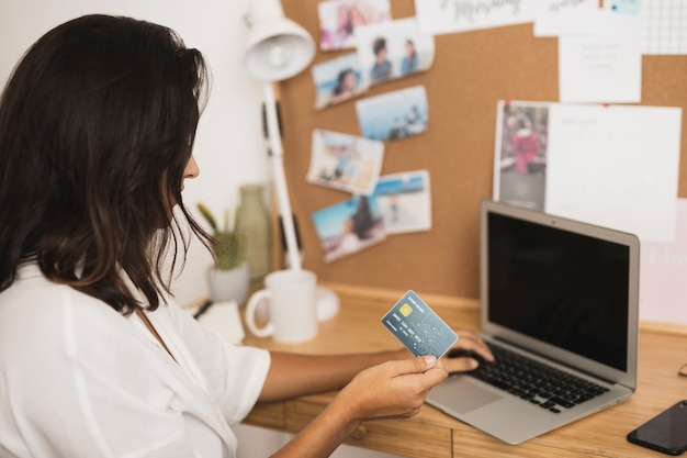 Woman holding a card and working on laptop mock up Free Photo