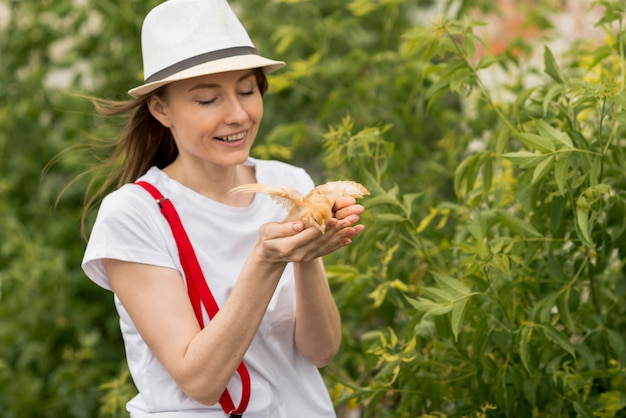 Woman holding a chick on a farm Free Photo